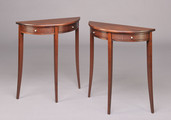 A pair of custom demi-lune side tables in mid stained Mahogany with Quilted Makore drawer fronts.