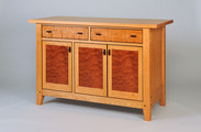 Chalford Farmhouse Sideboard.  Shown here with Quitled Makore door panels, Curly Cherry drawer fronts, hand-carved Wenge pulls and tenon pegs. Wenge stringing around drawers and doors.