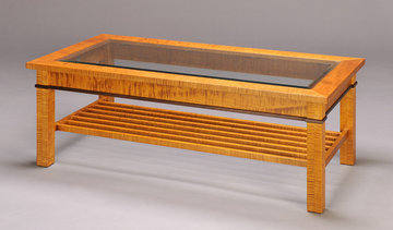 Gloucester Coffee Table. 52 x 26 x 18H. Shown in light stained Curly Maple with Ebonized apron inlay. Beveled glass top.