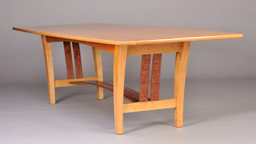 Fountain Brook dining table shown in Cherry with matched Bubinga curved slats.