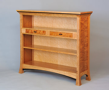 Pinnacle bookcase. Shown in Cherry with Bird's Eye Maple back, Curly Cherry sides and slide fronts and Wenge detailing. Adjustable lower shelf.