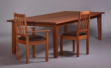Sapele dining table and low-back chairs. Brown leather seats.