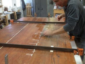 Raw floor boards clamped and glued.